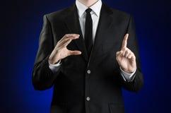 Zakenman en gebaaronderwerp: een mens in een zwart kostuum en een wit overhemd die gebaren met handen op een donkerblauwe achterg Royalty-vrije Stock Foto's