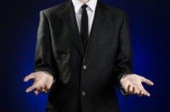 Zakenman en gebaaronderwerp: een mens in een zwart kostuum en een wit overhemd die gebaren met handen op een donkerblauwe achterg Stock Afbeeldingen