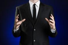 Zakenman en gebaaronderwerp: een mens in een zwart kostuum en een wit overhemd die gebaren met handen op een donkerblauwe achterg Stock Fotografie