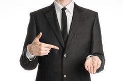 Zakenman en gebaaronderwerp: een mens in een zwart kostuum met een band toont de rechtse wijsvinger op zijn linkerhand op geïsole Stock Fotografie