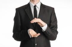 Zakenman en gebaaronderwerp: een mens in een zwarte die kostuum en bandholding dient voorzijde in op witte achtergrond in studio  Stock Fotografie
