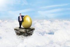 Zakenman en gouden ei op wolken stock foto's
