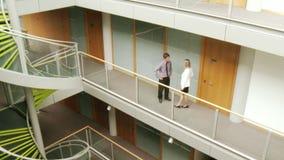 Zakenman en onderneemster die in een groot gebouw op elkaar inwerken stock footage