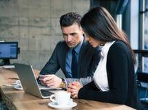 Zakenman en onderneemster die laptop in koffie met behulp van royalty-vrije stock foto's