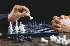 Zakenman en onderneemster het spelen schaak en het denken over s stock foto