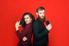 Zakenman en onderneemster met gadgets die op rode achtergrond wordt geïsoleerd stock foto