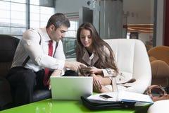Zakenman en onderneemster op vergadering met laptop en tablet Stock Afbeelding