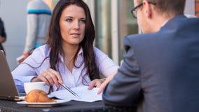 Zakenman en onderneemsters die een vergadering in koffie hebben. Hij ondertekent een contract. stock foto