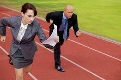 Zakenman en vrouw bij het lopen op rasspoor Stock Afbeeldingen
