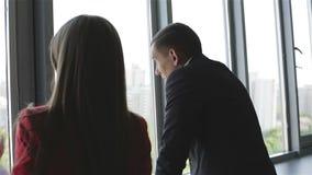 Zakenman en vrouw die en zich dichtbij het venster bevinden spreken stock video