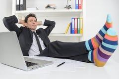 Zakenman in funky sokken. Zekere zakenman die zijn le houden Royalty-vrije Stock Afbeeldingen