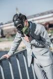 zakenman in gasmasker die probleem met ademhaling op brug en het leunen op traliewerklucht hebben stock foto