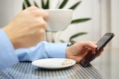Zakenman gebruikend mobiele telefoon en drinkend koffie Royalty-vrije Stock Foto's