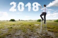 Zakenman gebruikend treden en bespuitend witte wolk met shap van 2018 Royalty-vrije Stock Afbeeldingen