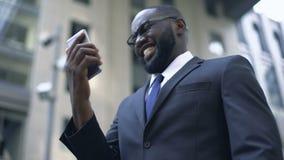 Zakenman gelukkig om geld te winnen, gebruikend smartphone voor weddenschappen en online handel drijvend stock footage