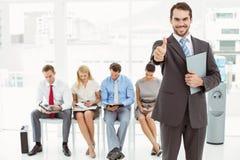 Zakenman gesturing duimen omhoog tegen mensen die op gesprek wachten Stock Foto's