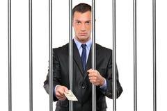 Zakenman in gevangenis die steekpenning geeft stock fotografie