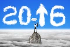 Zakenman golvende vlag op bergpiek met de wolkenhemel van 2016 Stock Afbeelding