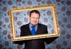 Zakenman in gouden frame op behang stock foto's