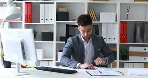 Zakenman in grijze jasjezitting bij lijst in wit bureau die, die document ondertekenen en document vliegtuig maken
