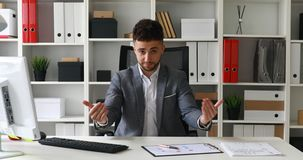 Zakenman in grijze jasjezitting bij lijst in wit bureau en het bekijken camera