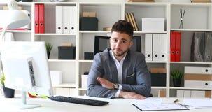 Zakenman in grijze jasjezitting bij lijst in wit bureau en het schudden hoofd negatief