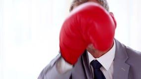 Zakenman het in dozen doen met rode handschoenen stock video