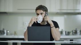 Zakenman het drinken koffie en sprekende telefoon thuis Bedrijfs mobiele mensenvraag stock videobeelden
