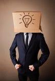 Zakenman het gesturing met een kartondoos op zijn hoofd met ligh stock foto