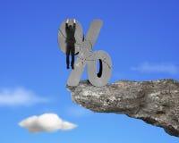 Zakenman het hangen op gebarsten percentageteken met klippenhemel Royalty-vrije Stock Foto
