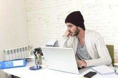 In zakenman in het koele hipster beanie kijken aan laptop computermonitor die project analyseren Royalty-vrije Stock Foto's