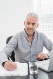 Zakenman het schrijven neemt van terwijl het gebruiken van laptop bij bureau nota Royalty-vrije Stock Foto