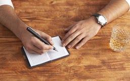 Zakenman het schrijven notitieboekje het schrijven whisky stock afbeeldingen