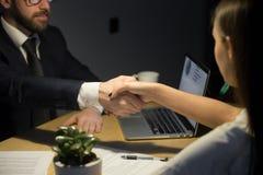 Zakenman het schudden hand van vrouwelijke partner in bureau royalty-vrije stock afbeeldingen