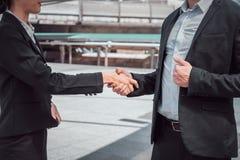 Zakenman het schudden handen met bedrijfsvrouw voor het aantonen van hun overeenkomst om contract tussen hun bedrijven te onderte royalty-vrije stock afbeelding