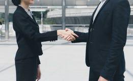 Zakenman het schudden handen met onderneemster voor het aantonen van hun overeenkomst om overeenkomst tussen hun bedrijven te ond stock afbeeldingen