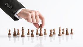 Zakenman het spelen schaak die donker koningsstuk bereiken bij witte tabl stock fotografie