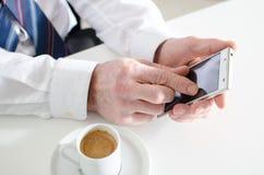 Zakenman het texting met smartphone en het drinken van een koffie Royalty-vrije Stock Afbeelding