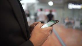 Zakenman het texting op smartphone, die online winkelen terwijl anderen zich in lijn bevinden stock video