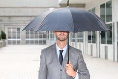 Zakenman het verbergen onder een paraplu in bureauruimte royalty-vrije stock fotografie