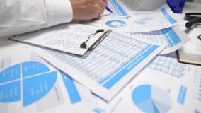 Zakenman het werken en het berekenen, lezen en schrijven rapporten Bureauwerknemer, lijstclose-up Bedrijfs financi?le boekhouding stock video