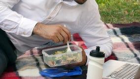 Zakenman het wsiting op groen gras, die lunch eten, royalty-vrije stock foto
