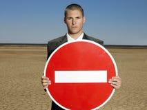 Zakenman Holding 'Geen Ingangs' Teken in Woestijn Stock Afbeeldingen