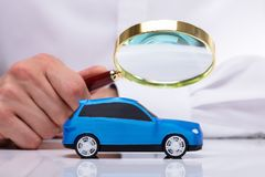 Zakenman Holding Magnifying Glass over Auto stock afbeelding
