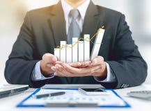Zakenman huidige het groeien grafiek op hand met businessplan royalty-vrije stock afbeelding
