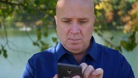 Zakenman Image Text Using Cellphone en het Kijken Zeker aan Camera stock videobeelden