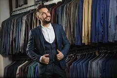 Zakenman in klassiek vest tegen rij van kostuums in winkel Stock Fotografie