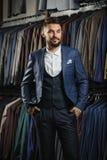 Zakenman in klassiek vest tegen rij van kostuums in winkel Royalty-vrije Stock Fotografie