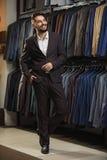 Zakenman in klassiek vest tegen rij van kostuums in winkel Royalty-vrije Stock Afbeelding