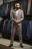 Zakenman in klassiek vest tegen rij van kostuums in winkel Stock Foto's